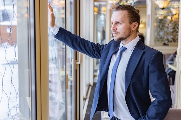 Handsome man in the suit  standing and looking serious  in the window indoor