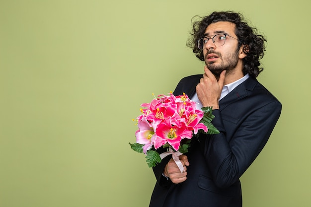 Handsome man in suit with bouquet of flowers looking aside puzzled