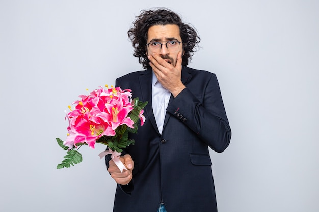 Handsome man in suit with bouquet of flowers looking being shocked covering mouth with hand