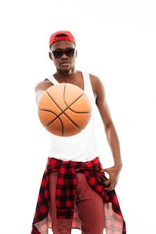 Uomo bello in occhiali da sole che dà la palla di pallacanestro a voi