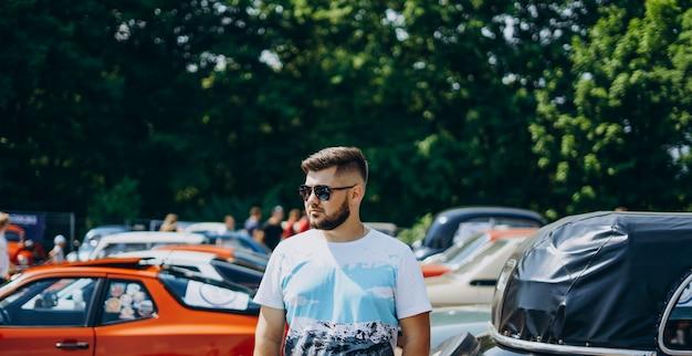 Handsome man in sunglasses near retro cars.
