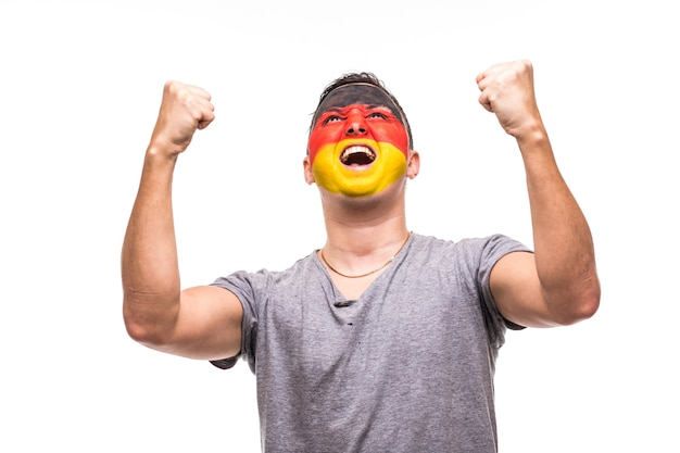 Handsome man supporter fan of germany national team with painted flag face get happy victory screaming into a camera. fans emotions.