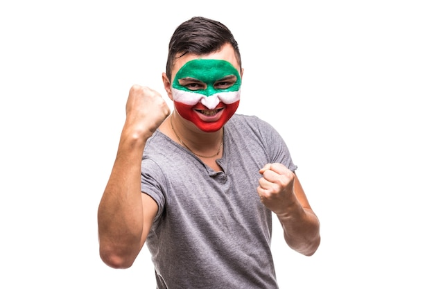 Handsome man supporter fan of iran national team painted flag face get happy victory screaming into a camera. fans emotions.