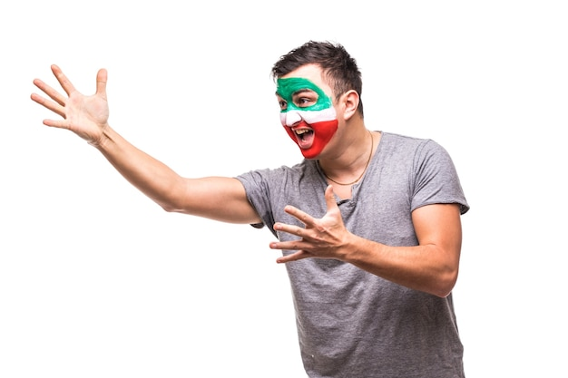 Handsome man supporter fan of iran national team painted flag face get happy victory screaming pointed with hand. fans emotions.