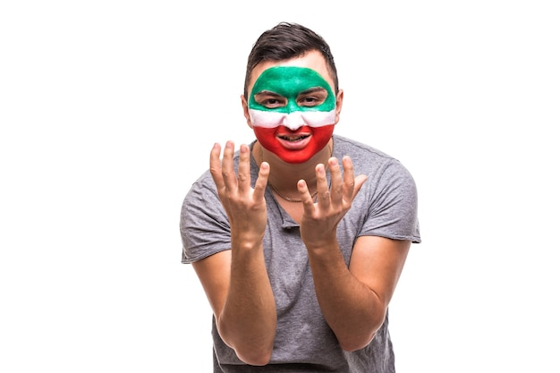 Handsome man supporter fan of iran national team painted flag face get unhappy sad frustrated emoitions into a camera. fans emotions.