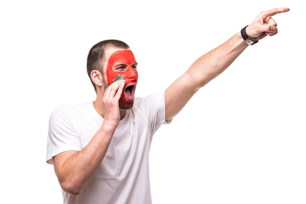 Handsome man supporter fan of morocco national team painted flag face get happy victory screaming pointed with hand. fans emotions.