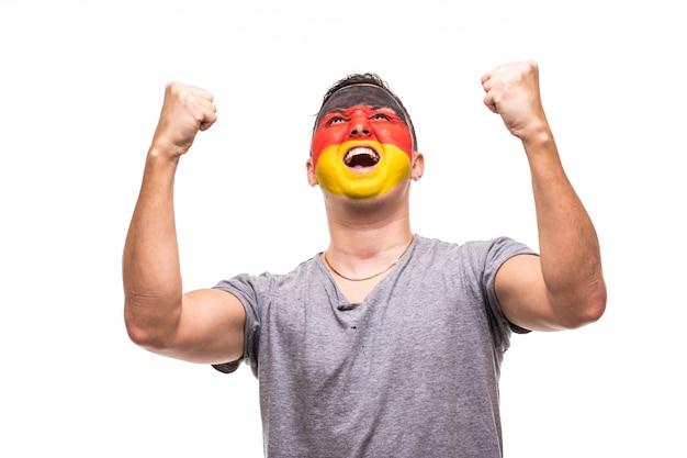 旗の顔が描かれたドイツ代表のハンサムな男性サポーターファンは、カメラに向かって叫んで幸せな勝利を手に入れます。ファンの感情。