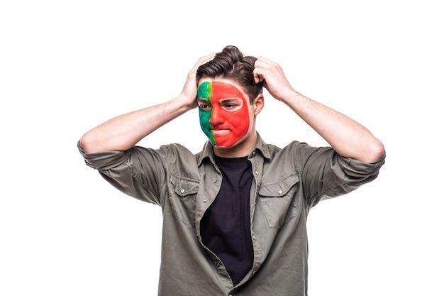ポルトガル代表のハンサムな男性サポーターファンが旗の顔を描いて、カメラに不幸な悲しい欲求不満の感情を取得します。ファンの感情。