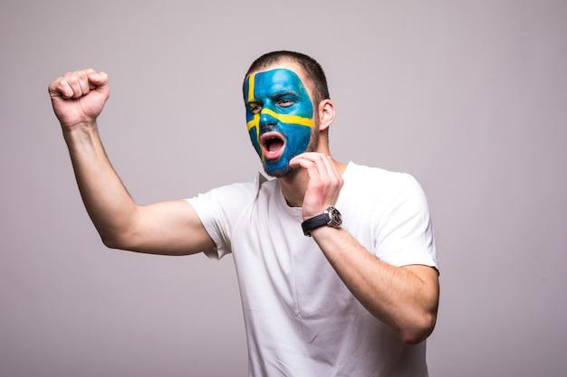 旗の顔を描いたスウェーデン代表のハンサムな男のサポーターファンは、とがった手を叫んで幸せな勝利を得る。ファンの感情。