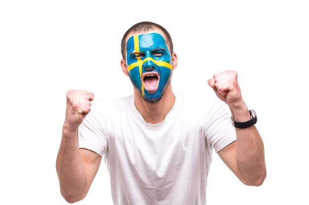Handsome man supporter fan of sweden national team with painted flag face get happy victory screaming into a camera. fans emotions.