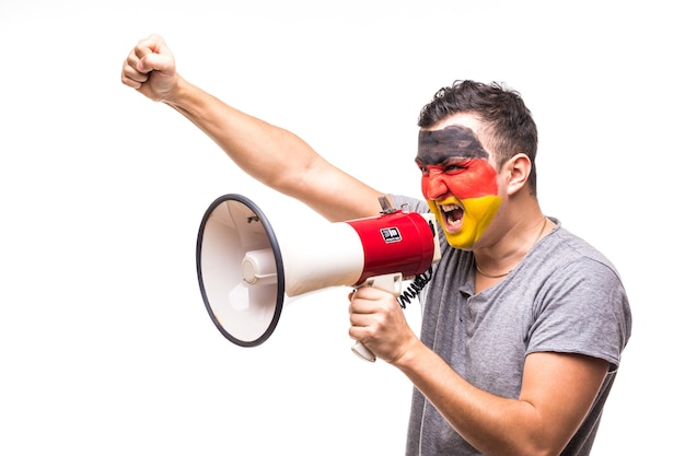 Handsome man supporter loyal fan of germany national team with painted flag face get happy victory screaming into megaphone with pointed hand. fans emotions.
