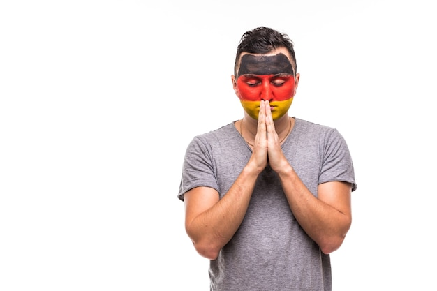 Handsome man supporter loyal fan of germany national team with painted flag face pray on white. fans emotions.