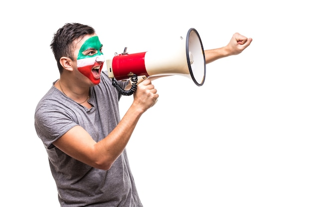 Handsome man supporter loyal fan of iran national team painted flag face get happy victory screaming into megaphone with pointed hand. fans emotions.