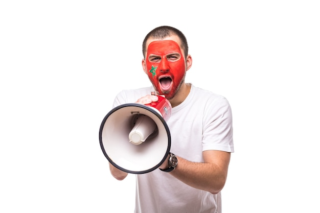 Handsome man supporter loyal fan of morocco national team painted flag face get happy victory screaming into megaphone with pointed hand. fans emotions.