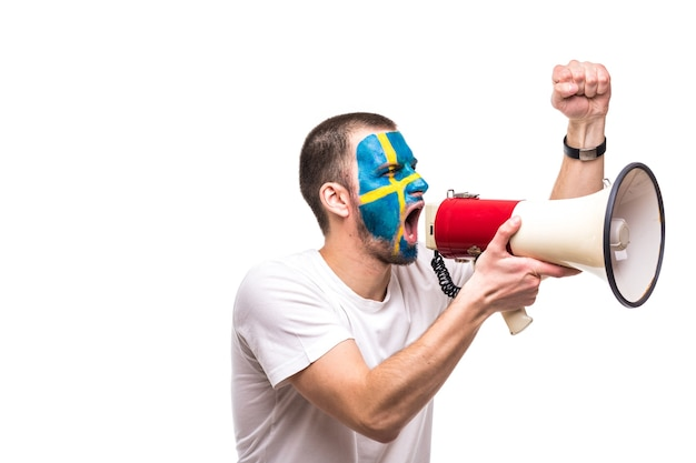 Handsome man supporter loyal fan of sweden national team with painted flag face get happy victory screaming into megaphone with pointed hand. fans emotions.