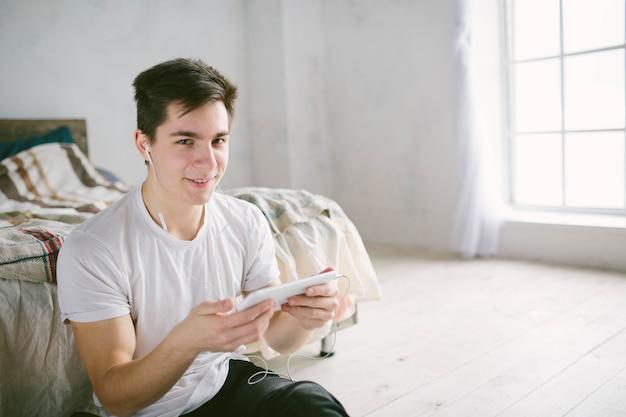 タブレットでサーフィンするハンサムな男。友達と話している男、ビデオ会議、スカイプ、タブレット。若い学生はソーシャルネットワークをスクロールします。
