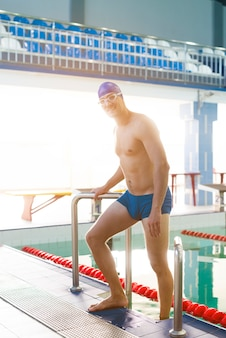 Handsome man swimmer exiting swimming pool