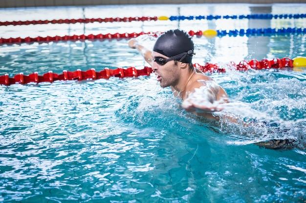 Красивый мужчина плавает в бассейне