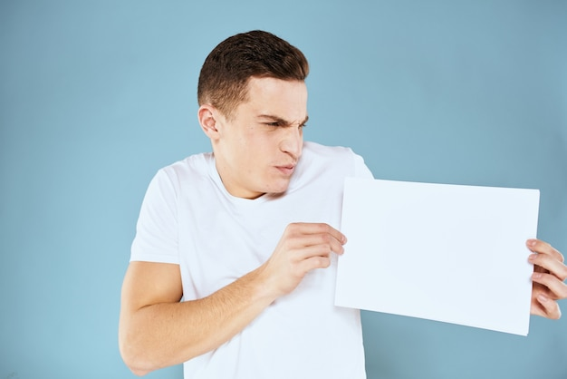 Handsome man in a t-shirt holds a white sheet without an inscription, free space, empty space, copy space