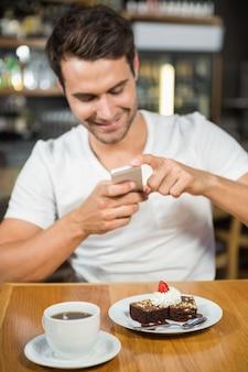 Красивый человек фотографируя его еда