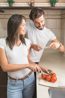 Handsome man taking picture of girlfriend cutting vegetables