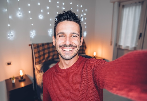Handsome man taking selfie at home