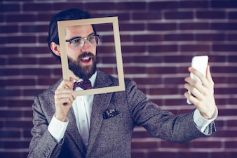Handsome man taking selfie through cellphone while holding frame against brick wall