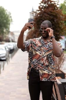 야외에서 현대 스마트폰으로 셀카를 찍는 잘생긴 남자