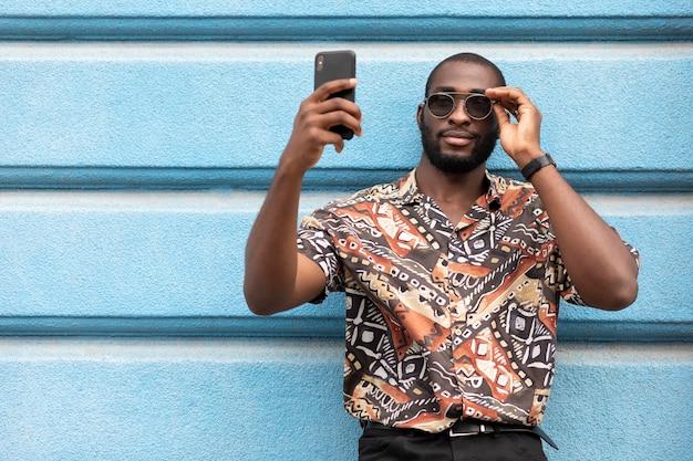 Bell'uomo che si fa selfie con uno smartphone moderno all'aperto
