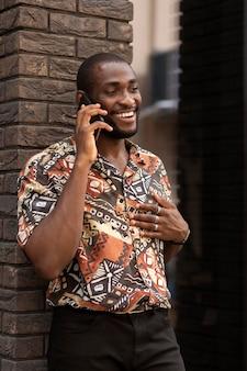 야외에서 전화 통화를 하는 잘생긴 남자