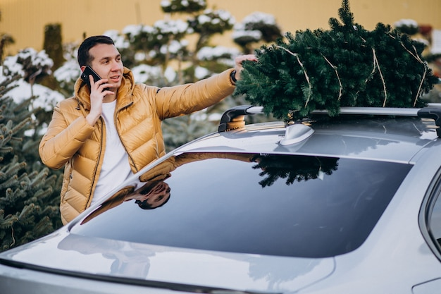 Handsome man talking on phone by the car with christmas tree on top
