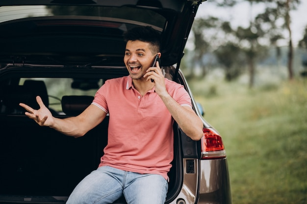 Handsome man talking on the phone by the car