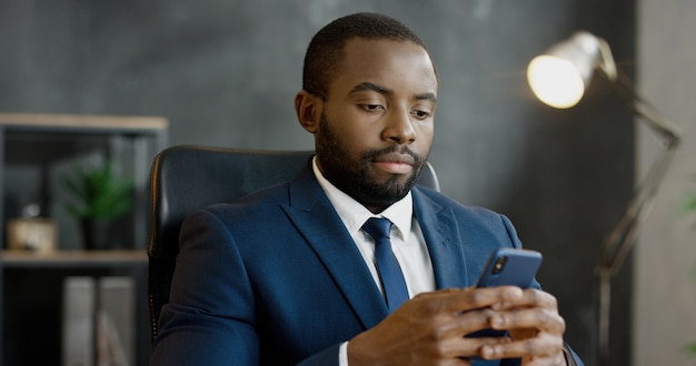 Handsome man tapping and scrolling on mobile phone in office.