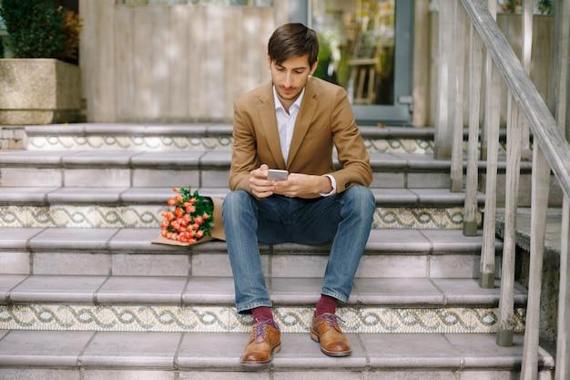 携帯電話を見ながらハンサムな男のテキストメッセージ