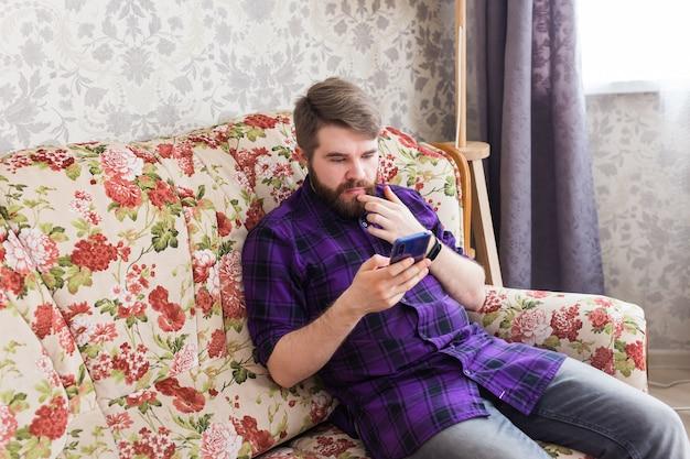 居間で彼のスマートフォンでテキストメッセージを送るハンサムな男