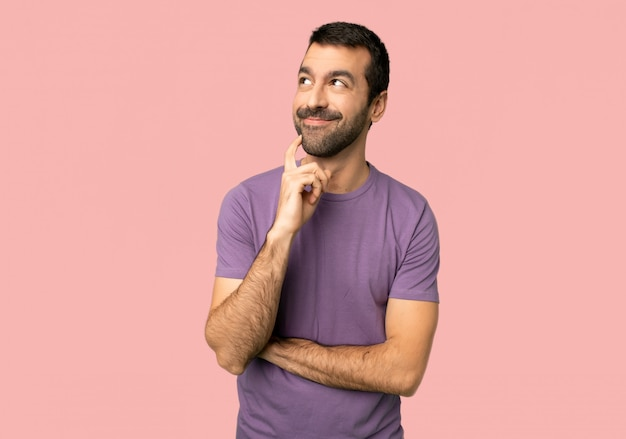 Handsome man thinking an idea while looking up on isolated pink background