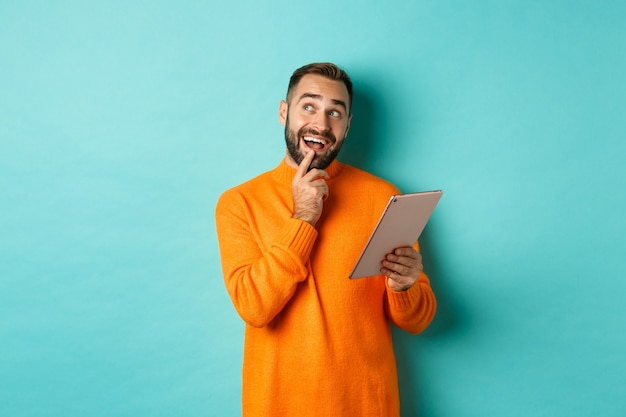 Bell'uomo pensando e utilizzando la tavoletta digitale, acquisti online e riflettendo idee