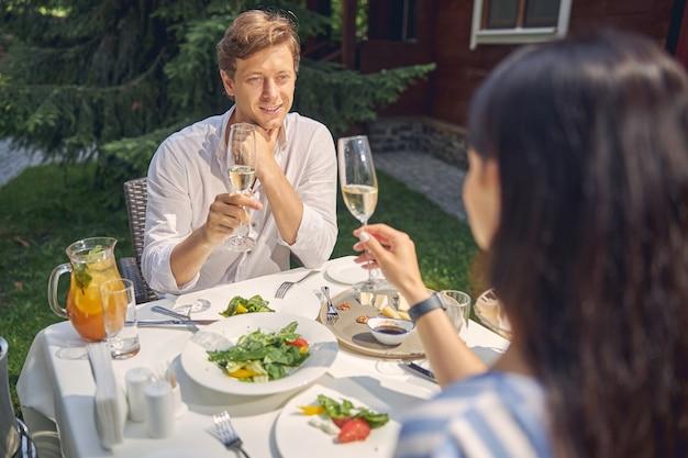 레스토랑에서 아름다운 아가씨와 함께 시간을 보내는 동안 와인 잔을 토스트하는 잘 생긴 남자 프리미엄 사진