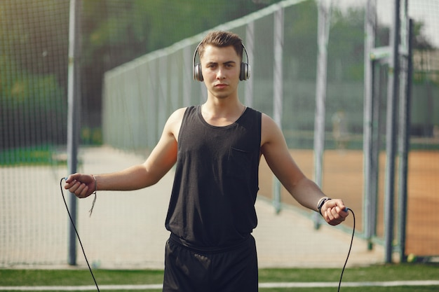 Handsome man training in a summer park with a jump rope