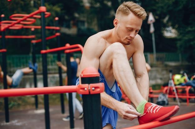 Handsome man training in a summer park