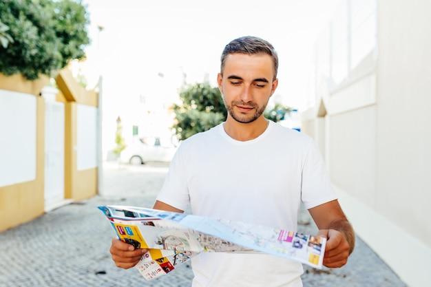 Красивый мужчина-путешественник нашел правильное направление на карте, гуляя с камерой в городских условиях