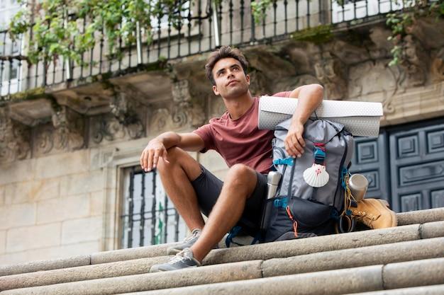 彼のバックパックと一緒に旅行するハンサムな男