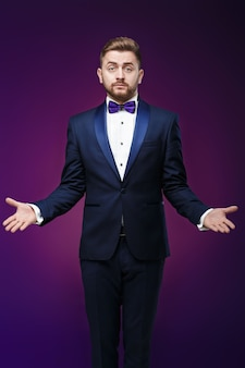 Handsome man in tuxedo and bow tie is surprised throws his hands compere in fashionable festive clothing