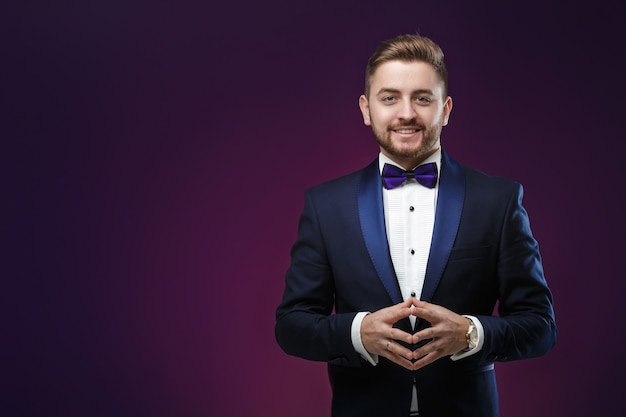 Handsome man in tuxedo and bow tie looking at camera fashionable festive clothing emcee on dark