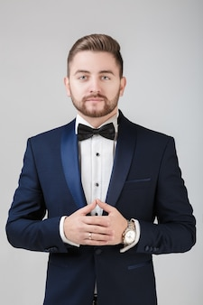 Handsome man in tuxedo and bow tie looking at camera fashionable festive clothing emcee on grey