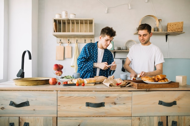 Handsome man using cellphone standing near his friend cutting apple on wooden counter