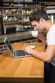 Handsome man using laptop and having coffee