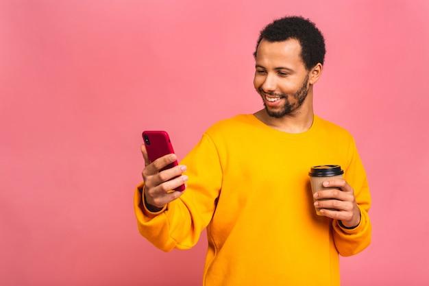 Красивый мужчина с помощью мобильного телефона и питьевой забрать кофейную чашку. изолированный над розовым.
