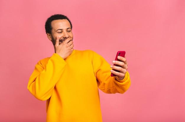 Красивый мужчина с помощью мобильного телефона и питьевой кофе на вынос