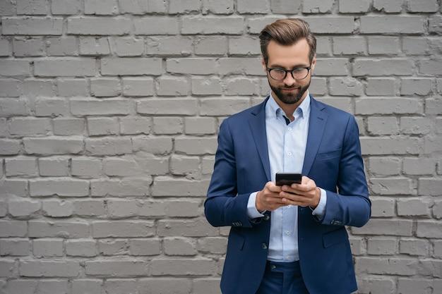 Красивый мужчина с помощью мобильного телефона, делая покупки онлайн текстовыми сообщениями, стоя у стены электронная коммерция